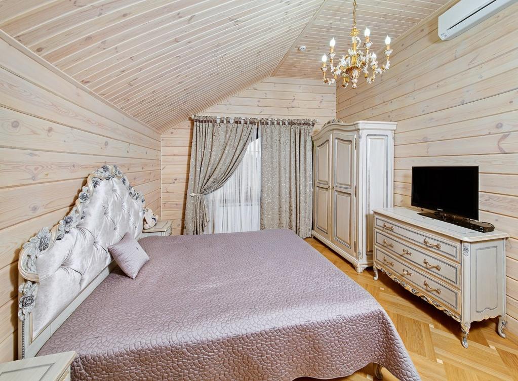 Интерьер спальни в светлых тонах, расположенной на втором этаже дома