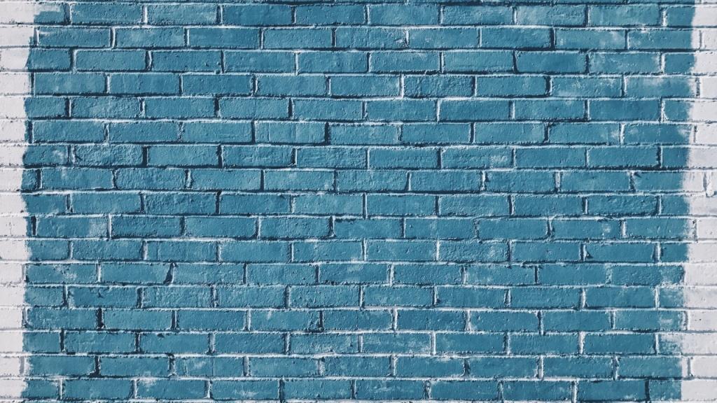 Фото: нанесение голубой краски на обработанную кирпичную стену