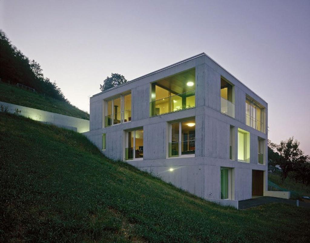Дизайн двухэтажного коттеджа простой геометрической формы удивительно гармонично смотрится на фоне склона