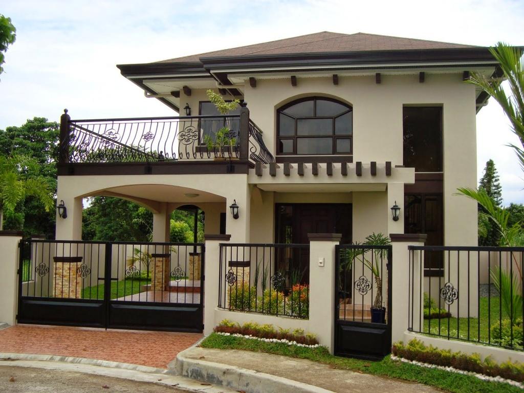 В отделке этого элегантного загородного коттеджа использована простая белая штукатурка, на фоне которой великолепно выглядят кованые перила балкона и ограда. Цвет черепицы и крыши идеально поддерживает дизайн