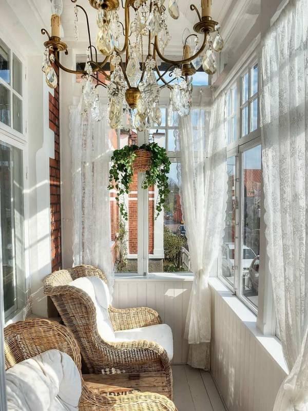белый балкон с люстрой и плетеной мебелью