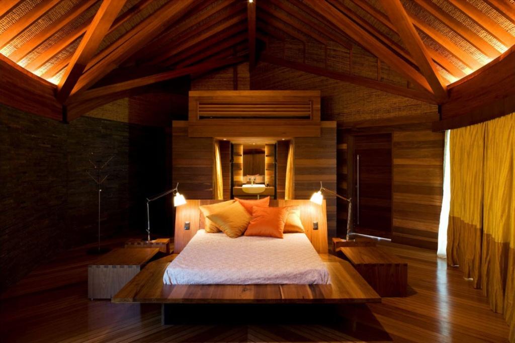 Интерьер спальни в темных тонах, расположенной на мансардном этаже