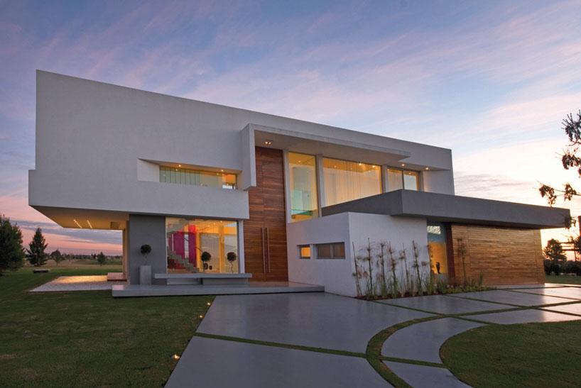 На фото показан двухэтажный коттедж в стиле минимализм, построенный из бетона. Это один из самых подходящих материалов для реализации проектов современного направления