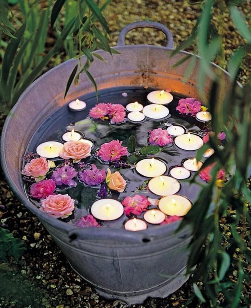 наполненное водой ведро с бутонами и свечами